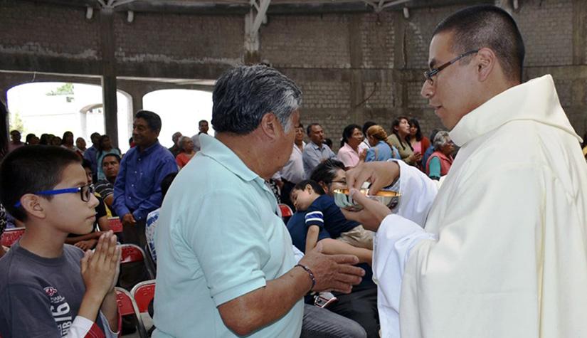 Alehandro gives Holy Communion