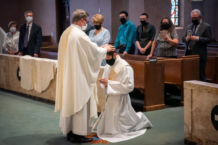 Father Mannara lays his hands on newly ordained Father Rivera