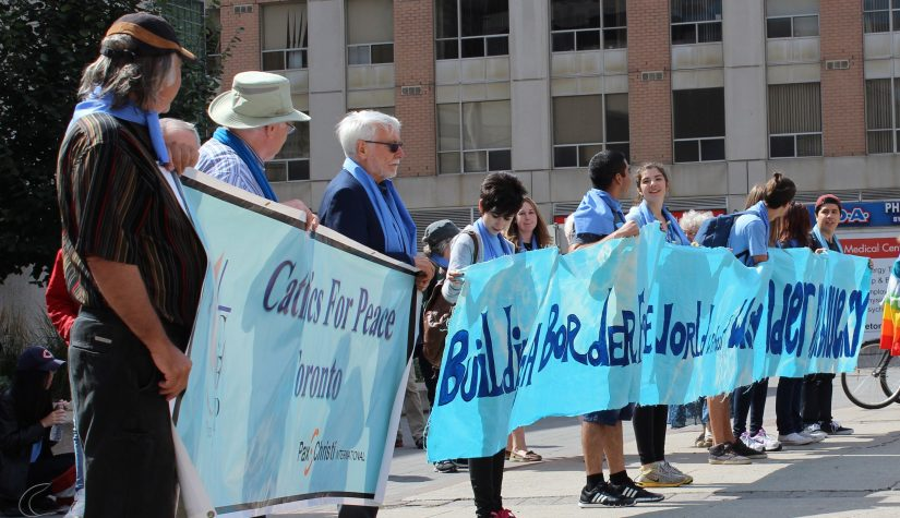 "Blue Scarf Walk participants hold up banner reading ""Building a Border Free World."""